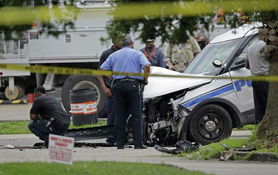 A handcuffed prisoner in a New Orleans police cruiser grabbed a gun, fatally shot the officer at the wheel and escaped, letting the vehicle crash into a utility pole. Photo: Gerald Herbert, STF / AP