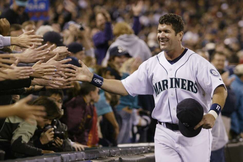 SEATTLE - OCTOBER 2:  Edgar Martinez #11 of the Seattle Mariners is greeted by fans as he takes a lap around the field during a post game ceremony honoring his career as a Mariner on October 2 2004 at Safeco Field in Seattle, Washington.   (Photo by Otto Greule Jr/Getty Images)