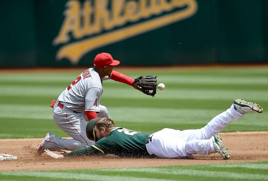 The A's Stephen Vogt slides safely with an RBI double in the first inning, beating the throw to the Angels' Erick Aybar. Photo: Thearon W. Henderson, Getty Images