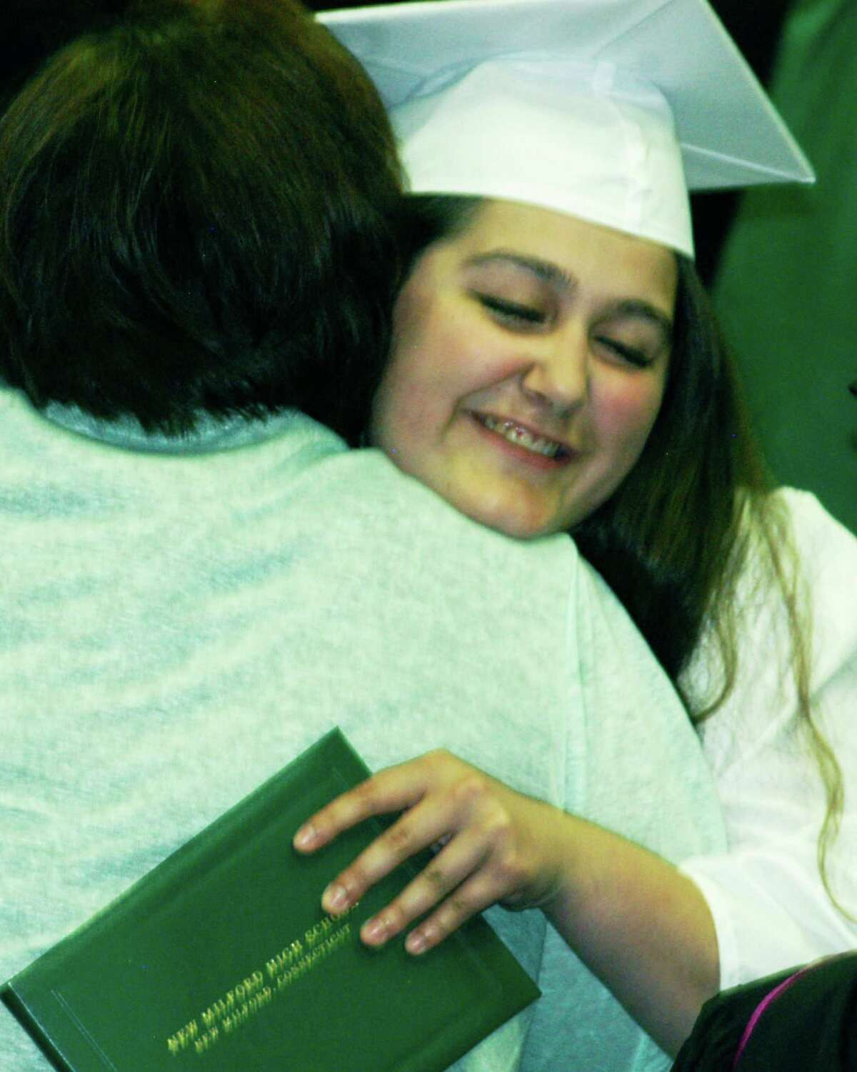 Amber Levine shares an emotional enmbrace Saturday with Class of 2015 advisor Daisy Norlander moments after receiving her diploma during the New Milford High School commencement ceremony at the O'Neill Center on the campus of Western Connecticut State University in Danbury. June 20, 2015