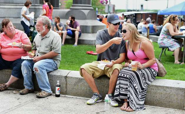 Jeff Hagars offers his girlfriend Sarah Killeen,right, both of Troy, one of his french fries during the annual Troy River Fest Saturday June 20, 2015 in Troy, NY.  (John Carl D'Annibale / Times Union) Photo: John Carl D'Annibale / 00032104A