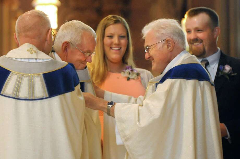 The Rev. Rick Lesser, second from left, is vested with holy garments on Saturday, June 20, 2015, at the Cathedral of the Immaculate Conception in Albany, N.Y. Joining him are his daughter Taryn Lesser, center, and son Evan Lesser, right. (Cindy Schultz / Times Union) Photo: Cindy Schultz / 00032345A