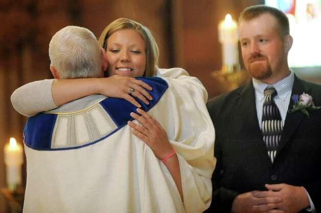 Taryn Lesser, center, embraces her father, The Rev. Rick Lesser, left, during his ordination to the priesthood on Saturday, June 20, 2015, at the Cathedral of the Immaculate Conception in Albany, N.Y. At right is his son Evan Lesser. His other son Craig Lesser is not pictured. (Cindy Schultz / Times Union) Photo: Cindy Schultz / 00032345A