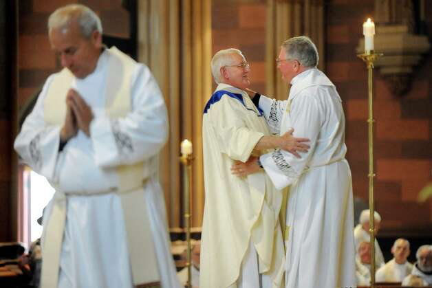 Fellow priests greet The Rev. Rick Lesser, center, as a sign of unity during his ordination to the priesthood on Saturday, June 20, 2015, at the Cathedral of the Immaculate Conception in Albany, N.Y. (Cindy Schultz / Times Union) Photo: Cindy Schultz / 00032345A