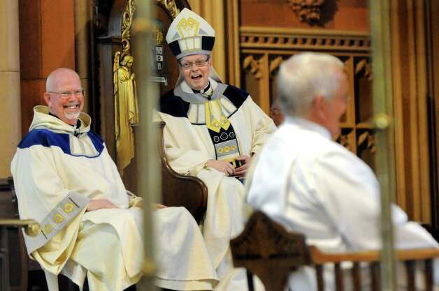 Bishop Edward Scharfenberger, center, teases Rick Lesser, right, who moved from deacon to priest during his ordination on Saturday, June 20, 2015, at the Cathedral of the Immaculate Conception in Albany, N.Y. (Cindy Schultz / Times Union) Photo: Cindy Schultz / 00032345A