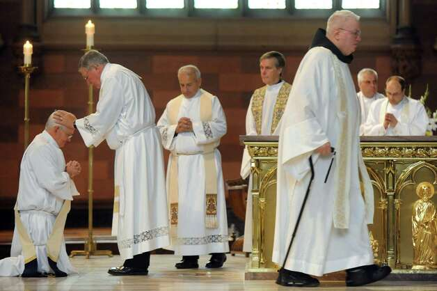 Priests place their hands on Rick Lesser as he moves from deacon to priest during his ordination on Saturday, June 20, 2015, at the Cathedral of the Immaculate Conception in Albany, N.Y. (Cindy Schultz / Times Union) Photo: Cindy Schultz / 00032345A