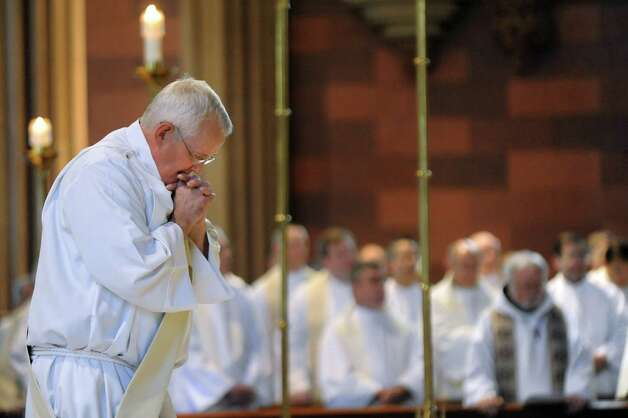 Rick Lesser, left, moves from deacon to priest during his ordination on Saturday, June 20, 2015, at the Cathedral of the Immaculate Conception in Albany, N.Y. (Cindy Schultz / Times Union) Photo: Cindy Schultz / 00032345A