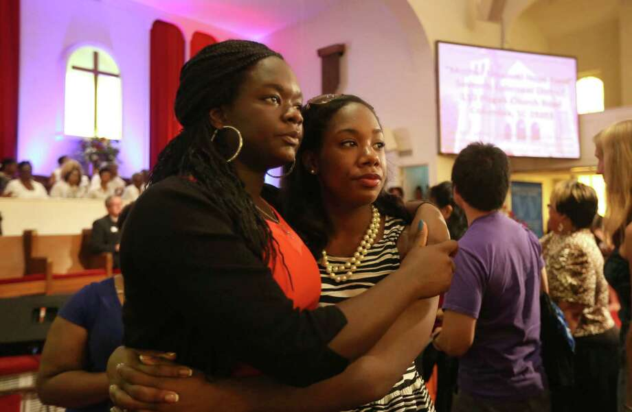 Sisters Julia and Lydia Anglin, of Katy, hug after giving an offering at the Texas Conference Ministers Alliance Houston Ecumenical Prayer Vigil at the Wesley African Methodist Episcopal Church Saturday, June 20, 2015, in Houston. The vigil was held in memory of the nine victims killed in the shooting at Emanuel AME Church in Charleston, South Carolina. Photo: Gary Coronado, Houston Chronicle / © 2015 Houston Chronicle
