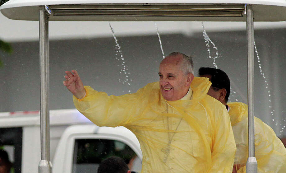"FILE - Wearing a yellow raincoat, Pope Francis waves to the faithful as he arrives in Tacloban, Philippines, Saturday, Jan. 17, 2015. Pope Francis called Thursday for a bold cultural revolution to correct what he calls the ""structurally perverse"" economic system of the rich exploiting the poor that is turning Earth into an ""immense pile of filth."" (AP Photo/Wally Santana) ORG XMIT: ALT102 Photo: Wally Santana / AP"