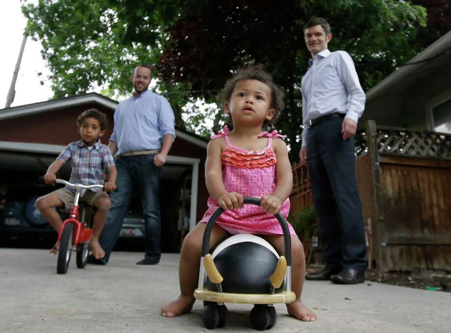Weston Clark, left, and his husband, Brandon Mark, right, play with their children Xander, 4, and Zoe, 17 months, at their home in Salt Lake City on Monday. Clark, 36, and Mark, 37, have been a couple for 15 years and are among a growing number of gay men raising children. Photo: Rick Bowmer, STF / AP