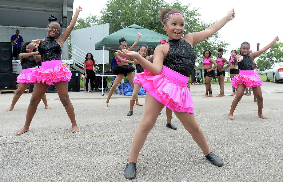 Members of Beaumont's Divine Steps Diamonds Battle team, including Jeanne Chauvin, 10, (foreground) dance for the crowd at the City of Beaumont's annual Juneteenth celebration in Tyrrell Park Saturday. Families gathered under tents to enjoy the day-long festivities, cooking out as they enjoyed the entertainment and activities for children. June 19 marks the final abolition of  slavery in the United States. Though the Emancipation Proclamation had  been made 2 years prior, Texas was slow to the rights of former slaves.  June 19, federal troops marched into Galveston to enforce the law, finally bringing the era of slavery to a close.  Photo taken Thursday, June 18, 2015 Kim Brent/The Enterprise Photo: Kim Brent / Beaumont Enterprise