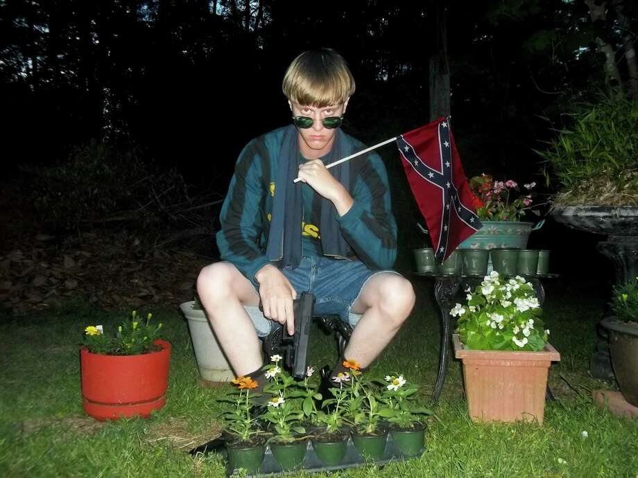 This undated image that appeared on Lastrhodesian.com, a website being investigated by the FBI in connection with Charleston, S.C., shooting suspect Dylann Roof, shows Roof posing for a photo while holding a Confederate flag. The website surfaced online Saturday, June 20, 2015, and also contained a hate-filled 2,500-word essay that talks about white supremacy and concludes by saying the author alone will need to take action. (Lastrhodesian.com via AP) MANDATORY CREDIT Photo: HONS / Lastrhodesian.com