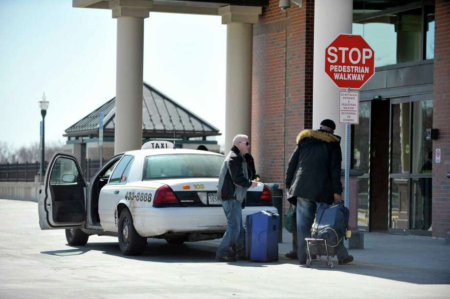 A cab driver with Buzzys Transportation drops travelers off at the Rensselaer Train Station on Thursday, April 2, 2015, in Rensselaer, N.Y.   (Paul Buckowski / Times Union) Photo: PAUL BUCKOWSKI / 00031288A