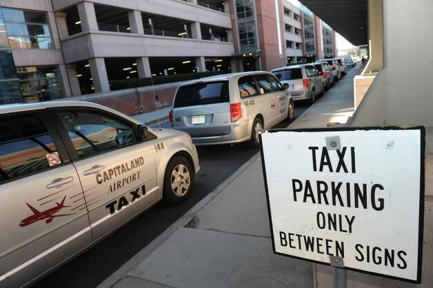 Official airport contracted taxis line up for pick ups at the Albany International Airport on Friday April 3, 2015 in Colonie, N.Y. (Michael P. Farrell/Times Union) Photo: Michael P. Farrell / 00031317A