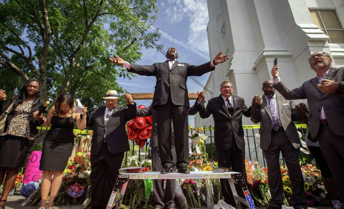 Dr. Dexter Easley preaches to a crowd gathered outside the Emanuel AME Church during a prayer service by the National Clergy Council on Saturday. Clergy from around the country led prayers and words of hope to the people in attendance.