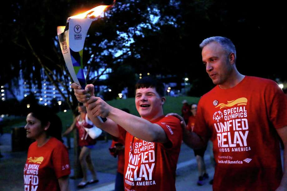Jonah Hickman, a 17-year-old Special Olympics athlete, carries the torch Saturday through Discovery Green with his father, Tim, in the Flame of Hope ceremony.  Photo: Gary Coronado, Staff / © 2015 Houston Chronicle