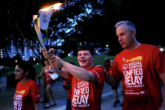 Jonah Hickman, a 17-year-old Special Olympics athlete, carries the torch Saturday through Discovery Green with his father, Tim, in the Flame of Hope ceremony.