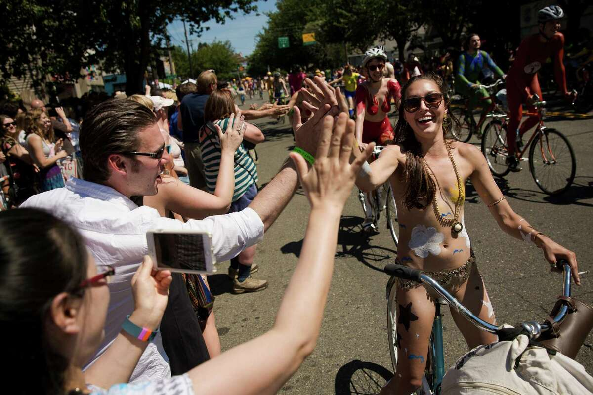Onlookers high-five naked bicyclists as they ride by during the 27th annual Fremont Solstice Parade, photographed Saturday, June 20, 2015, in Seattle. As part of the Fremont Fair, the parade set the tone for the first day of summer on June 21.