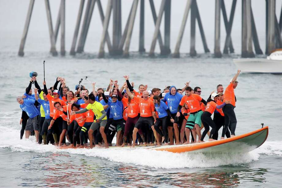 Surf's up, and so is the old record for most people riding on a surfboard. Sixty-six surfers from around the world hung loose on a custom-built, 42-foot board Saturday off Huntington Beach, Calif., riding a wave for 12 seconds and breaking the world record of 47 riders set in Queensland, Australia, about 10 years ago. Photo: Danny Moloshok, FRE / AP Images