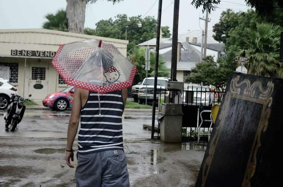 """Puro""(poo-row)PureRocking shorts and a tank top while holding an umbrella during a summer rainstorm at an open-air ice house is puro S.A. style. Photo: Mark A Zuniga, By Mark A. Zuniga, Sample 16, For MySA.com"