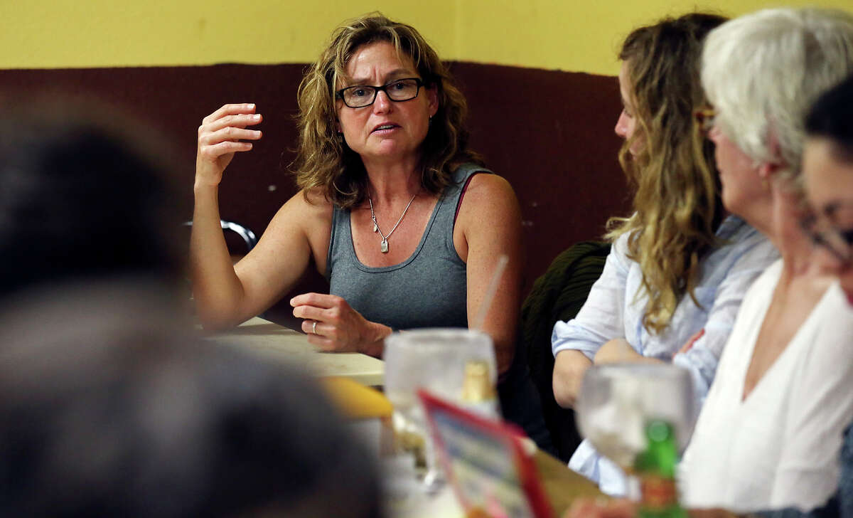 Lichter, (center) speaks with others involved in the pro bono legal effort for the immigrants during a dinner at a restaurant in Dilley.