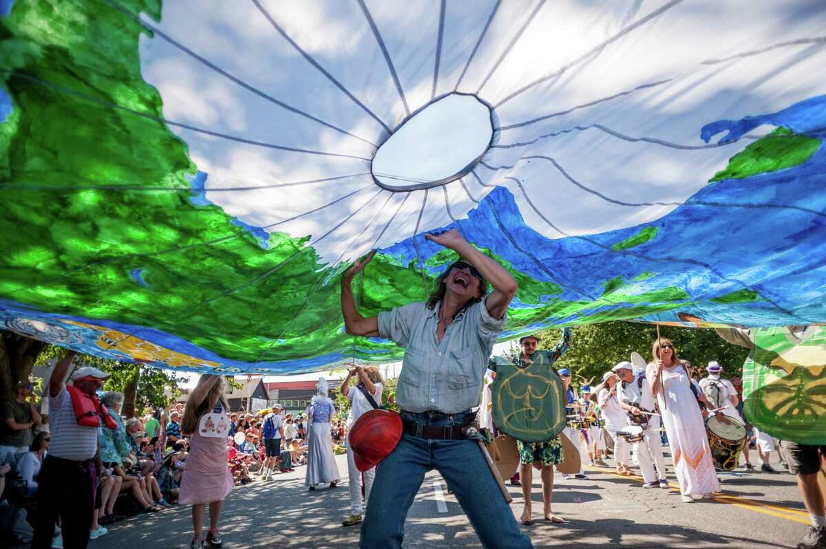A woman participates in a parachute attraction during the 27th annual Fremont Solstice Parade, photographed Saturday, June 20, 2015, in Seattle, Washington. As part of the Fremont Fair, the parade set the tone for the first day of summer on June 21.