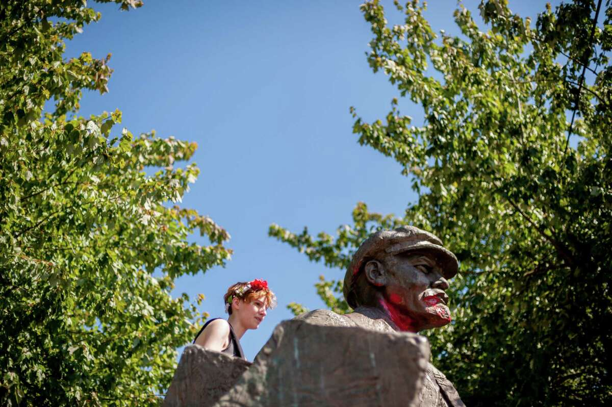 A woman climbs a statue of Vladimir Lenin during the 27th annual Fremont Solstice Parade, photographed Saturday, June 20, 2015, in Seattle, Washington. As part of the Fremont Fair, the parade set the tone for the first day of summer on June 21.