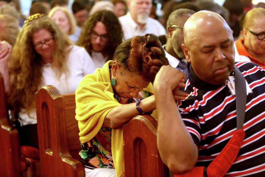 Jackie Pennie, center, of Missouri City, prays along with other guests Saturday at a vigil at the Wesley African Methodist Episcopal Church  in memory of the nine victims killed in the shooting at a Church in Charleston, S.C.  Photo: Gary Coronado, Staff / © 2015 Houston Chronicle
