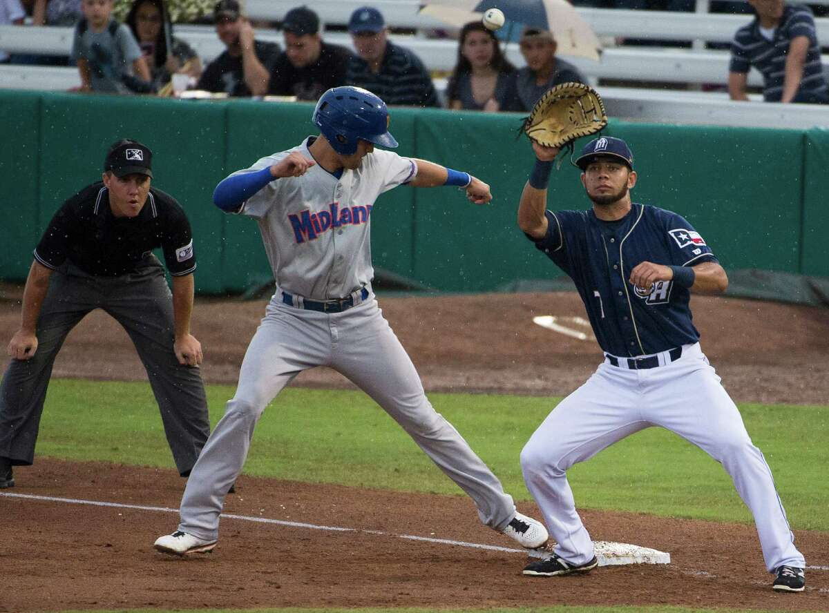 Midland's Chad Pinder (left) avoids a pickoff attempt as Missions first baseman Luis Domoromo catches the ball during Saturday's game.