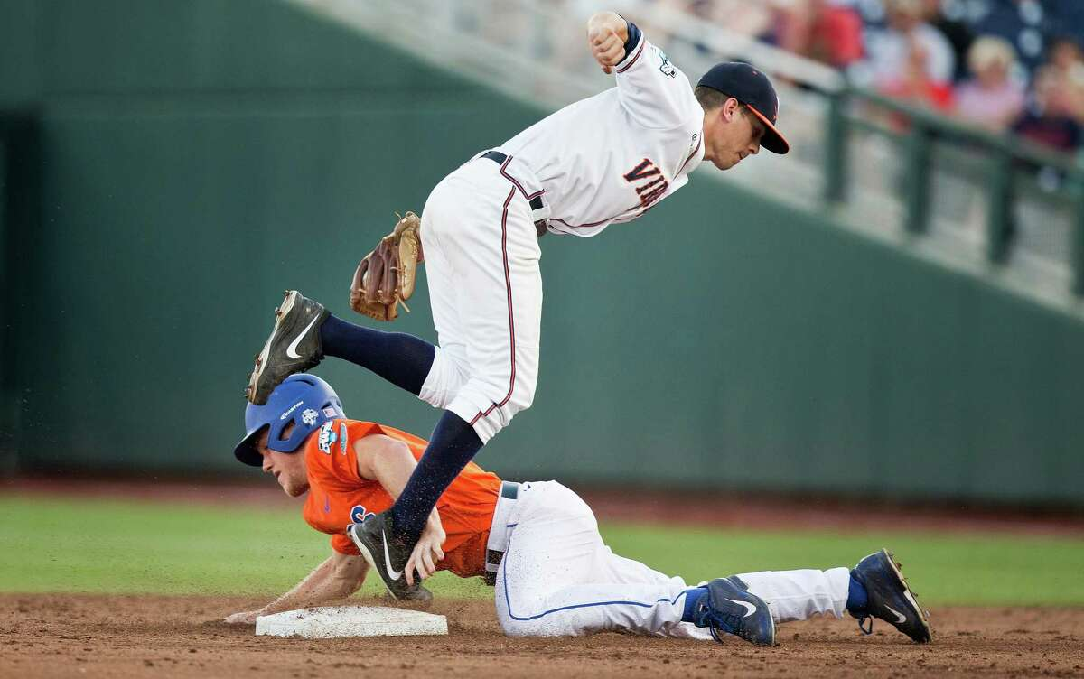 Virginia's Ernie Clement (4), top, tags out Florida's Harrison Bader (8) as he attempted to steal second base in the top of the third inning during game 13 of the College World Series at TD Ameritrade Park in Omaha, Neb., Saturday, June 20, 2015. (Mark Davis/The World-Herald via AP) MAGS OUT; ALL NEBRASKA LOCAL BROADCAST TELEVISION OUT
