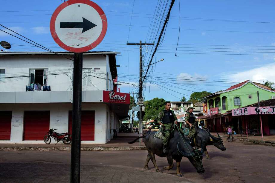 Military police patrol atop water buffalo, a longstanding practice on the island of Marajo, in Soure, Brazil, June 1, 2015. While the beasts thrive in the equatorial heat and are adept at navigating the island's swamplands, mounted officers claim another benefit — the presence of buffalo helps lower tensions between police and locals. (Marizilda Cruppe/The New York Times) Photo: MARIZILDA CRUPPE, STR / New York Times / NYTNS