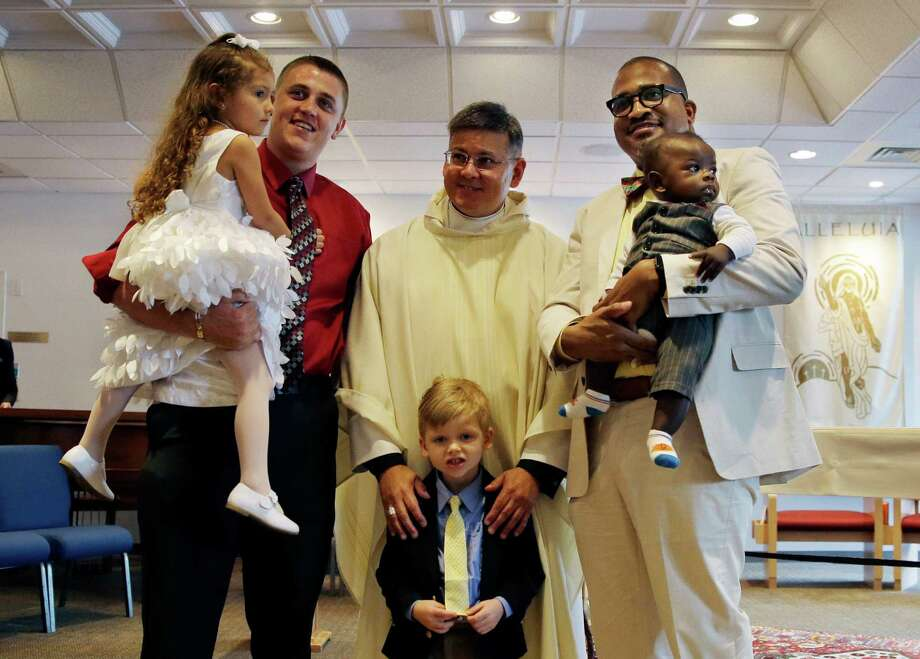Paul Yorgey, left, holds their daughter, Anabella Marie Yorgey-Girdy, 4, as his husband, Gregory Girdy, right, holds their son, Xander Cole Yorgey-Girdy, six-months, while their foster son, Shane Genay, 5, stands with St. Miriam's ordained pastor Father Jim St. George after Anabella's baptism ceremony at Saint Miriam church in Blue Bell, Pa. on Sunday, May 17, 2015. (AP Photo/Mel Evans) Photo: Mel Evans, STF / Associated Press / AP