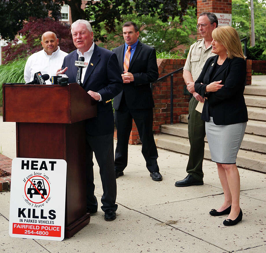 First Selectman Mike Tetreau is joined by other town officials to anounce a new sign campaign to remind drivers to check their cars for children and pets before they leave the car. Photo: Genevieve Reilly / Fairfield Citizen / Fairfield Citizen