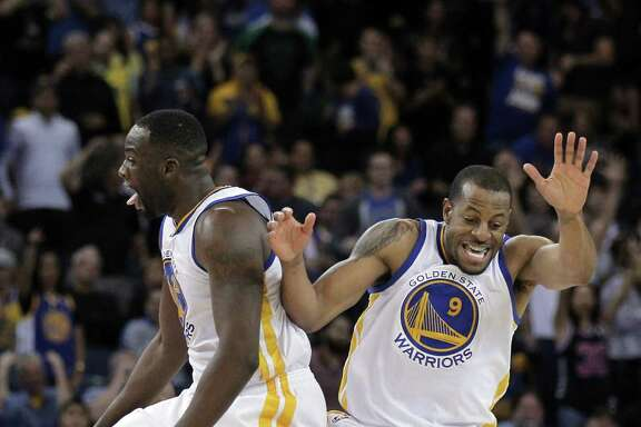 Andre Iguodala (9) and Draymond Green (23) celebrate Iguodala's fourth quarter dunk. The Golden State Warriors played the Detroit Pistons at Oracle Arena in Oakland, Calif., on Wednesday, March 11, 2015.