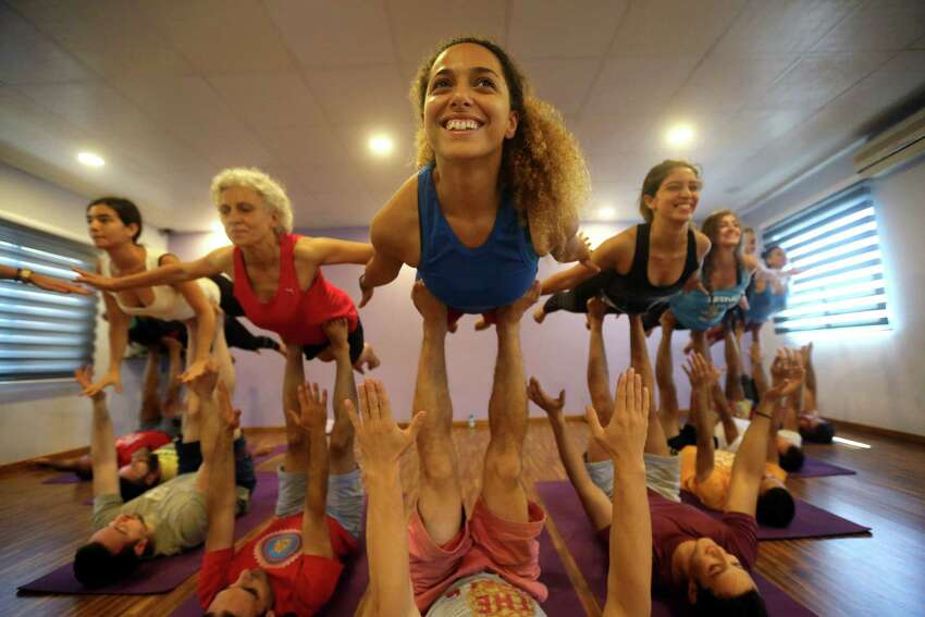 Lebanese and foreign citizens perform yoga during an Acro yoga class to mark International Yoga Day, at Beirut Yoga Center, Lebanon, Sunday, June 21, 2015. Millions of yoga enthusiasts across the world bent and twisted their bodies in complex postures Sunday to mark International Yoga Day.