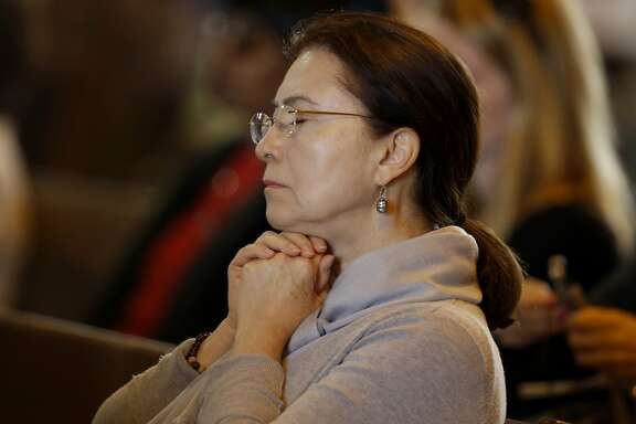 A woman shut her eyes as she listened to Father Brendan McBride Sunday June 21, 2015. Hundreds attended a memorial Mass at St. Mary's Cathedral in San Francisco, Calif. for the Irish nationals killed in the balcony-collapse in Berkeley and the victims of the South Carolina church massacre.