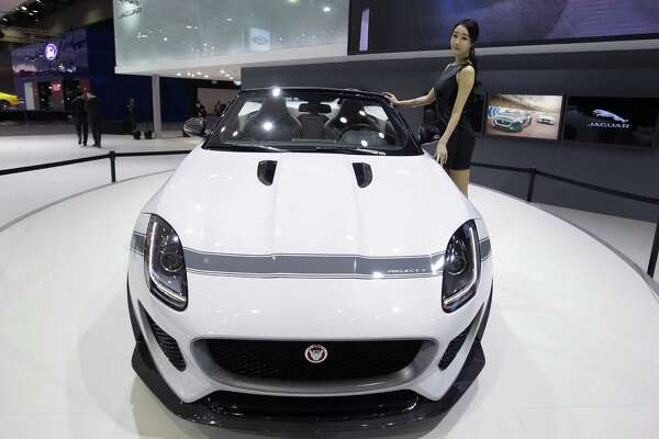 SEOUL, SOUTH KOREA - APRIL 02: A model poses next to a Jaguar Project 7 at the Seoul Motor Show 2015 at KINTEX on April 2, 2015 in Seoul, South Korea. The Seoul Motor Show 2015 will be held in April 2 to April 12, featuring state-of-the-art technologies and concept cars from global automakers. The show is in its tenth year and now features 32 brands.