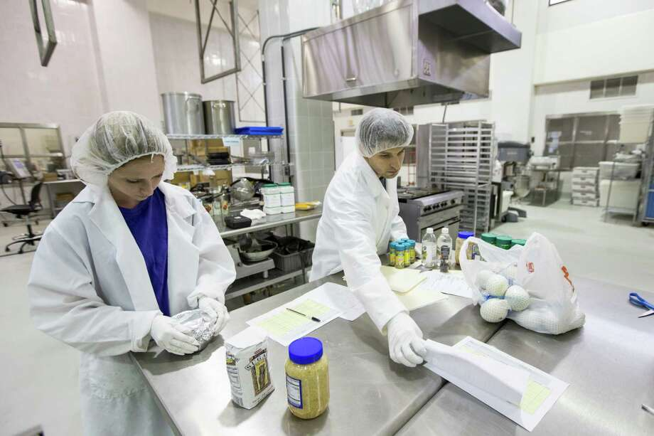 Jennifer Sawyer, student technician, left, and Ben O'Neil, food scientist, work on preparing food to be sent to the International Space Station at the National Center for Electron Beam Research at Texas A&M Univerisity on Tuesday, June 9, 2015, in College Station. ( Brett Coomer / Houston Chronicle ) Photo: Brett Coomer, Staff / Houston Chronicle / © 2015 Houston Chronicle