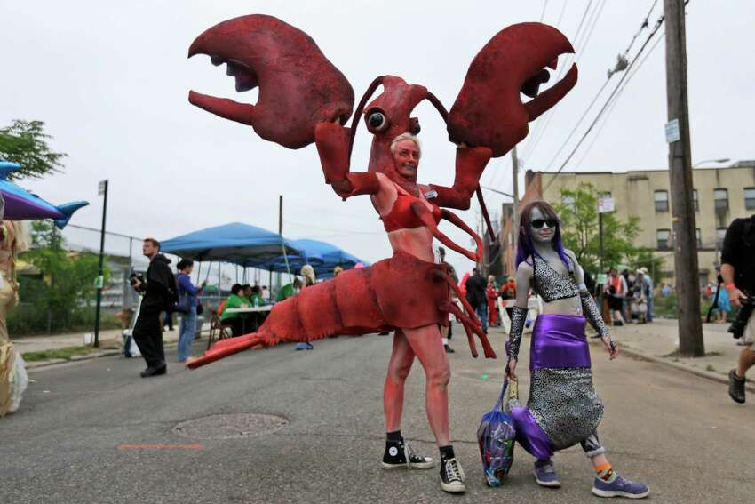 Katherine Gates, left, as a Lobster, and her daughter Lucy Warner, 8, as a mermaid, pose for photographers in the staging area, Saturday, June 20, 2015, in New York's Coney Island. The parade, which began in 1983 and takes place on the Saturday closest to the first day of summer, is a mix of seaside honky-tonk and family fun.