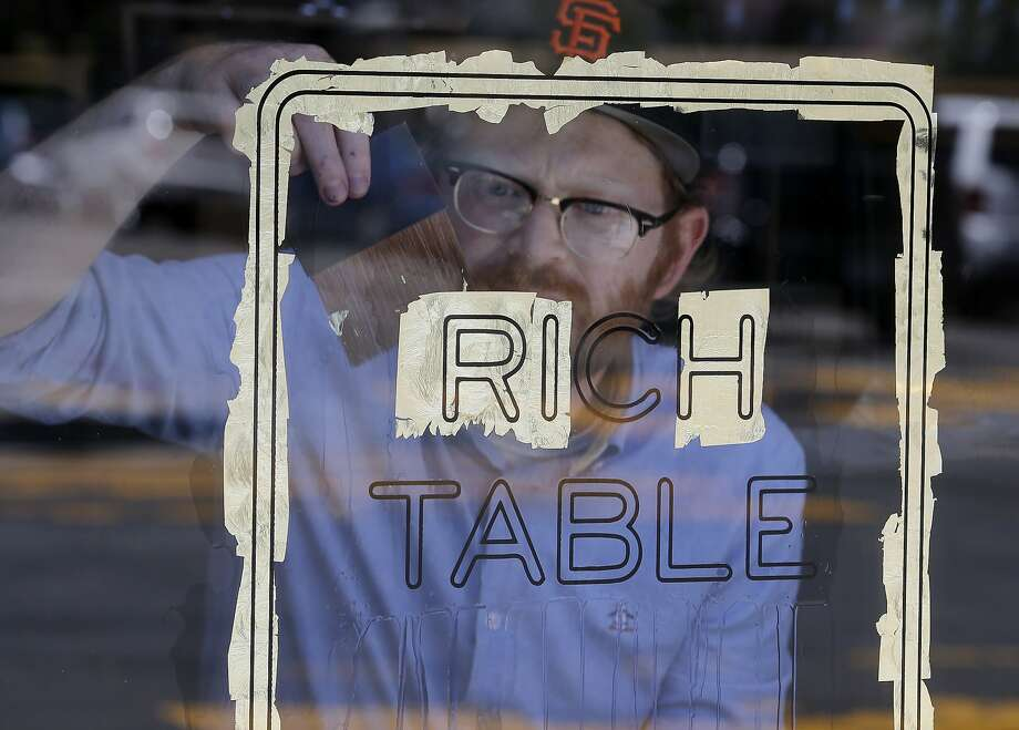 Andrew Lawrence applies gold leaf to his sign Thursday June 18, 2015. Andrew Lawrence is the man behind Gentleman Scholar Signs.  He makes ornate, etched, gold-leaf window signs for San Francisco, Calif. restaurants. Photo: Brant Ward, The Chronicle