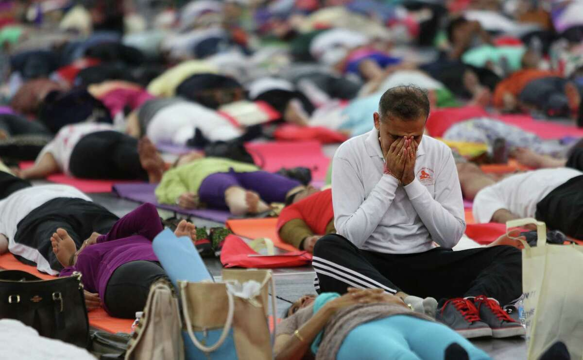 Participants meditate during a collective yoga session during International Day of Yoga at the George R. Brown Convention Center on Sunday, June 21, 2015, in Houston.