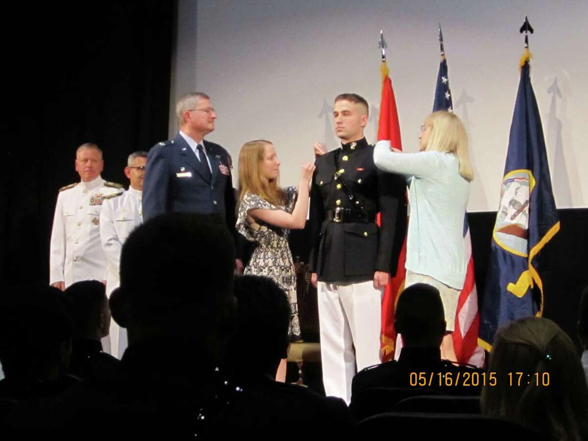 Courtesy Reid C. Muller of Colonie receives his Marine second lieutenant ensignias from his sister, Aislinn Muller, and his mother, during his commissioning ceremony at the Eastman House, Rochester. The Marine father, retired Air Force Col. Reid T. Muller, left, had administered his son?s officer oath,