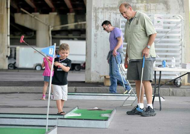 Brad Maione from Delmar and his son, Daniel, 4, play miniature golf at the Corning Preserve during Dad Fest on Sunday, June 21, 2015, in Albany, N.Y. The yearly Father's Day event is put on by the City of Albany.    (Paul Buckowski / Times Union) Photo: PAUL BUCKOWSKI / 00031889A