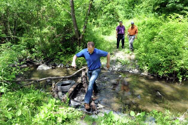 City Planning Director Charles Moore, left, leads engineer David Hiss, center, and engineer aide Mark Hendrick as they ford a creek on Wednesday, June 17, 2015, at the future Hollow Park in Rensselaer, N.Y. (Cindy Schultz / Times Union) Photo: Cindy Schultz / 00032288A