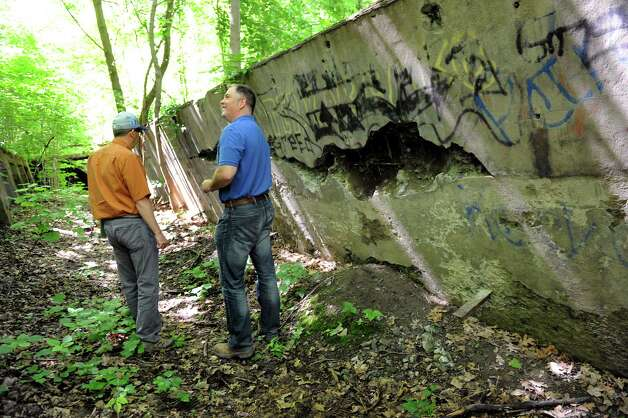 City Planning Director Charles Moore, right, and engineer aide Mark Hendrick look over the bunker on Wednesday, June 17, 2015, at the future Hollow Park in Rensselaer, N.Y. (Cindy Schultz / Times Union) Photo: Cindy Schultz / 00032288A