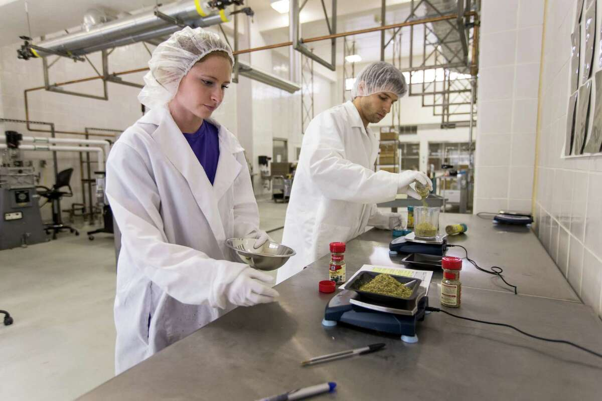 Student technician Jennifer Sawyer, left, and food scientist Ben O'Neil prepare food to be sent to the International Space Station at A&M's National Center for Electron Beam Research.