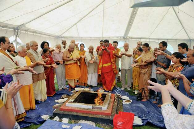 Members of the Hindu Temple Society and Hindu priests pray for devotion, education, success, knowledge, wealth, strength and long life during a fire ceremony during a celebration of the 39th anniversary of the Hindu Temple Society, on Sunday, June 21, 2015, in Loudonville, N.Y. During the fire ceremony participants throw offerings into the fire to symbolize that nothing belongs to them, everything belongs to the gods, and they are giving back to the gods and asking to be blessed. During the ceremony participants chanted to purify themselves and the universe.    (Paul Buckowski / Times Union) Photo: PAUL BUCKOWSKI / 00032234A