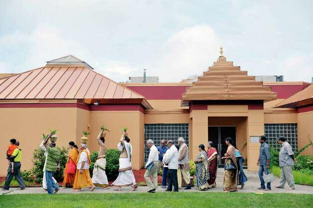 Members of the Hindu Temple Society and Hindu priests process around the outside of the Hindu Temple during a celebration of the 39th anniversary of the Hindu Temple Society, on Sunday, June 21, 2015, in Loudonville, N.Y. Some participants hold metal pots filled with water on their heads. The water that would be poured on the deities inside the temple to transfer energy to the gods.    (Paul Buckowski / Times Union) Photo: PAUL BUCKOWSKI / 00032234A