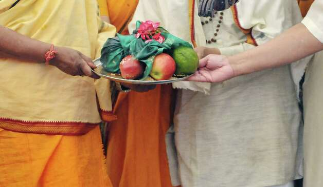 A plate of offerings is held over a fire during a fire ceremony during a celebration of the 39th anniversary of the Hindu Temple Society, on Sunday, June 21, 2015, in Loudonville, N.Y. During the fire ceremony participants throw offerings into the fire to symbolize that nothing belongs to them, everything belongs to the gods, and they are giving back to the gods and asking to be blessed. During the ceremony participants chanted to purify themselves and the universe.    (Paul Buckowski / Times Union) Photo: PAUL BUCKOWSKI / 00032234A