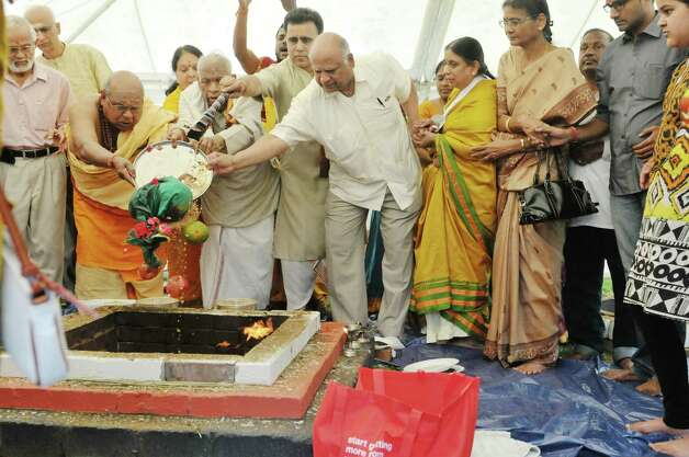 Members of the Hindu Temple Society and Hindu priests dump a plate of offerings into a fire during a fire ceremony during a celebration of the 39th anniversary of the Hindu Temple Society, on Sunday, June 21, 2015, in Loudonville, N.Y. During the fire ceremony participants throw offerings into the fire to symbolize that nothing belongs to them, everything belongs to the gods, and they are giving back to the gods and asking to be blessed. During the ceremony participants chanted to purify themselves and the universe.    (Paul Buckowski / Times Union) Photo: PAUL BUCKOWSKI / 00032234A